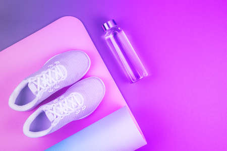 Top view of neon purple and pink colored white sport shoes sneakers, yoga mat, reusable eco glass water bottle with place for text. Yoga, pilates or fitness practice. Losing weight and sport concept.