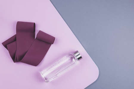 Top view of maroon expander elastic band, eco reusable glass water bottle on pink yoga mat over neutral grey background. Yoga pilates or fitness practice. Losing weight and sport concept.