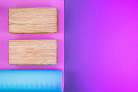 Top view of blue pink yoga mat and two wooden blocks on neon colored pink purple background. Yoga, pilates or sport concept. Flat Lay. Place for text.