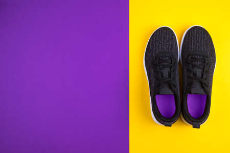 Top view of black sport shoes sneakers on purple violet yellow background. Losing weight and sport concept. Flat Lay.Copy space. Stock fotó