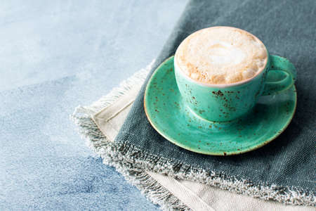 Cup of cappuccino on grey napkin on textured background. Morning coffee rituals. Place for text. Stock fotó