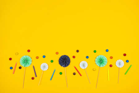 Birthday party festive background made of holiday supplies and round colorful candies on yellow. Top view. Copy space. Stock fotó