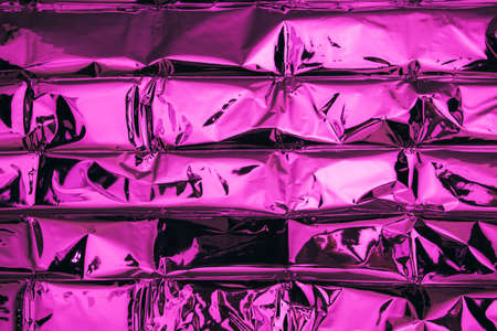 Top view of trendy background made of textured foil colored neon pink gradient. Abstract creative backdrop.