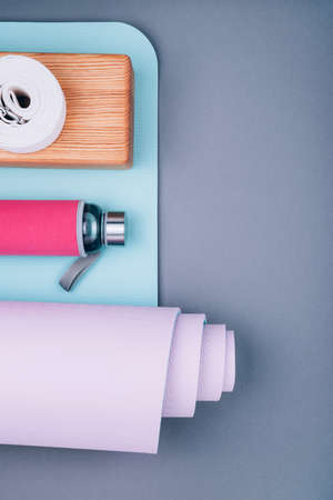 Top view of blue pink yoga mat,glass water bottle, wooden block and twisted white belt on grey background. Yoga pilates practice, relaxation and meditation accessories.