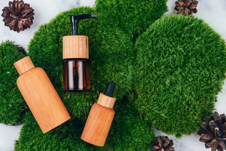 Top view of wooden and glass bottles containers blank mockup for skincare products on natural dark green moss over marble background decorated with pinecones. Zero waste life beauty spa concept. Stock fotó
