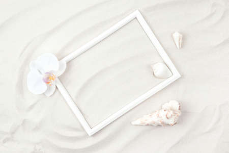 Top view of white photo frame on sand background decorated with orchid flowes and seashells. Summer and vacation concept. Flat lay. Copy space. Stock fotó