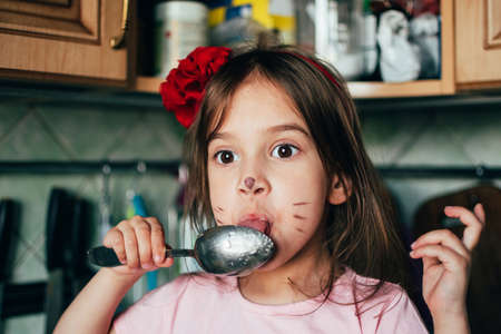 Cute toddler girl with face painting like a cat, licking spoon with honey in the kitchen. Real life moments. Fun in the kitchen with little helper. Stock fotó