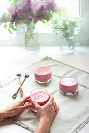 Womans hands holding glass of homemade berry smoothie on white napkins in the kitchen. Healthy breakfast. Rustic style. Stock fotó