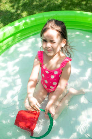 Cute little toddler girl playing in inflatable water pool on sunny day outdoor. Summer leisure concept. Happy childhood. Genuine lifestyle moments.