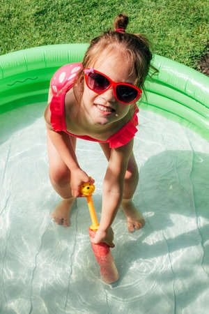Cute little toddler girl smiling playing in inflatable water pool on sunny day outdoor. Summer leisure concept. Happy childhood. Genuine lifestyle moments.