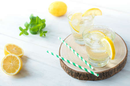 Two glasses of lemon homemade lemonade with mint leaves and ice on round wooden cut board on light background. Cool and fresh detox drink. Space for text.
