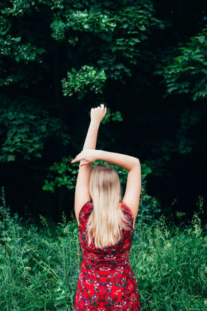 Young beautiful blonde long haired woman in red dress standing backwards with raised hands over green natural background outdoor. Freedom happiness concept. Place for text.