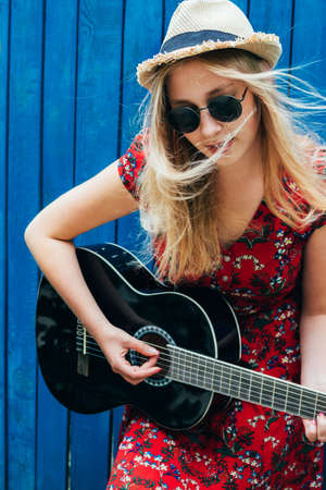 Beautiful teenage blonde long haired girl playing acoustic guitar outdoor over blue wooden fence. Youth concept.