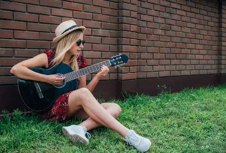 Pretty long haired blonde girl sitting on the grass and playing acoustic guitar outdoor near brick fence. Youth concept. Stock fotó
