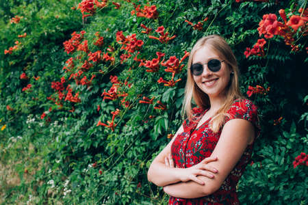 Portrait of young beautiful happy blonde long haired smiling teenage girl in sunglasses wearing red dress over green natural background outdoor. Freedom and happiness youth concept. Copy space. Stock fotó