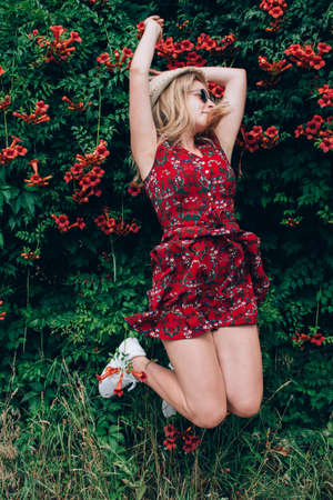 Young beautiful blonde long haired teenage girl in red dress jumping with raised hands over flowers natural background outdoor. Freedom happiness concept. Place for text.