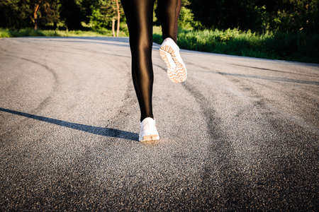 Feet of jogging woman in white sneakers shoes. Runner on road. Real life moments. Back view. Copy space.