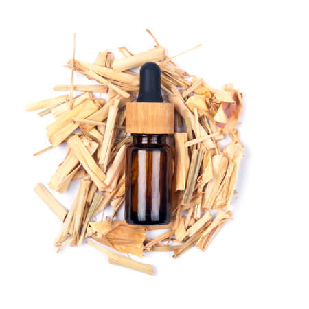 Top view of citronella essential oil in glass bottle on dried lemongrass sticks isolated on white background. Natural medicine aromatherapy.