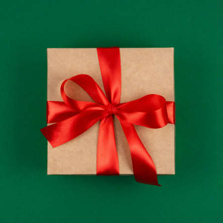 Top view of craft Merry Christmas gift with red bow ribbon over green background. Happy New Year greetings. Festive winter holidays backdrop. Flat lay. Happy Birthday card. Stock Photo