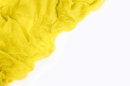 Top view of yellow colored gauze fabric isolated on white background with copy space. Trendy colors 2021 year. Flat lay.