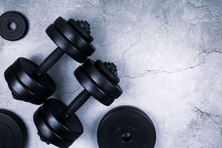 Top view of black dumbbells and different weight plates on gray textured background. Flat lay. Fitness or bodybuilding sport training concept. Copy space.