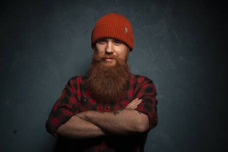 Red bearded man with orange hat and plaid shirt on the dark cyan background