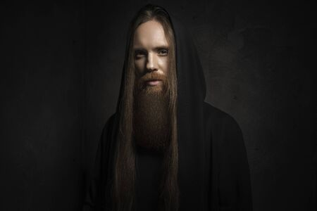 Man with long hair and beard in black hood on dark background