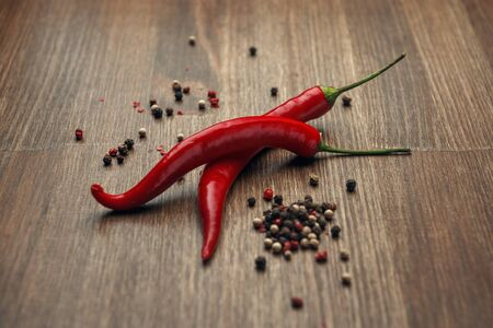 Two red ripe fruits of chili pepper and peppercorns on a wooden background
