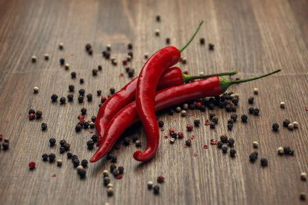 Three red ripe fruits of chili pepper and peppercorns on a wooden background