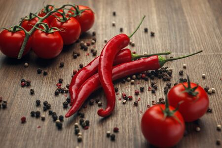 Red ripe fruits of chili pepper and cherry tomato with peppercorns on a wooden background