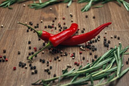 Red ripe fruits of chili pepper with peppercorns and rosemary on a wooden background