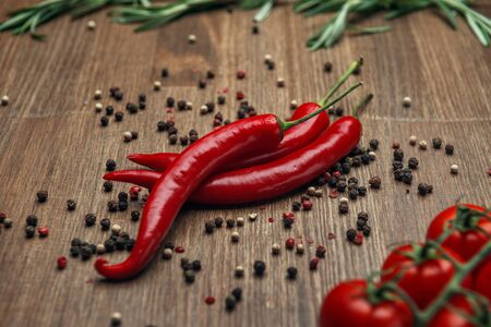 Red ripe fruits of chili pepper and cherry tomato with peppercorns and rosemary on a wooden background