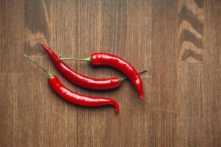 Three red ripe fruits of chili pepper on a wooden table Imagens
