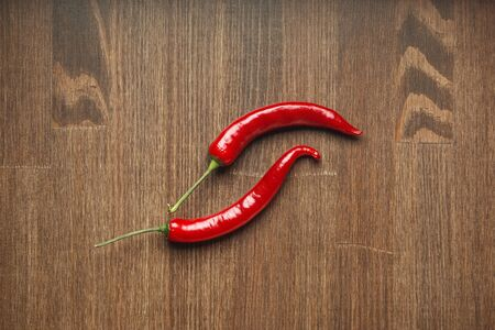 Two red ripe fruits of chili pepper on a wooden table