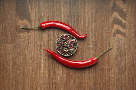 Two red ripe fruits of chili pepper and peppercorns on a wooden table