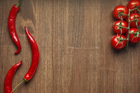 Red ripe fruits of chili pepper and cherry tomato on a wooden table Imagens