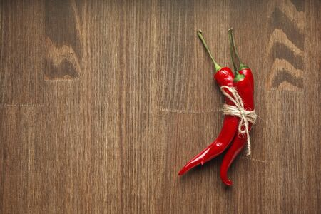Red ripe chili pepper fruits tied with craft linen rope on wooden background