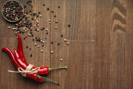 Red ripe chili pepper fruits tied with craft linen rope with peppercorns on wooden background