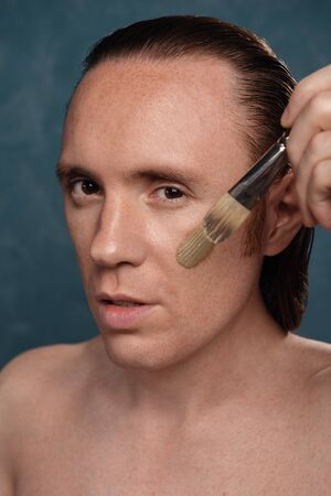 A man with long wet hair is applying a green clay mask with the visage brush. Stock Photo