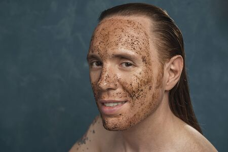 Smiling man with wet long hair in coffee mask on his face waiting of the spa procedures