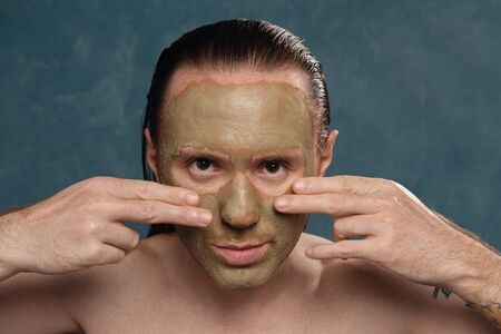 A tattooed man with long wet hair is applying a green clay mask with his hands.