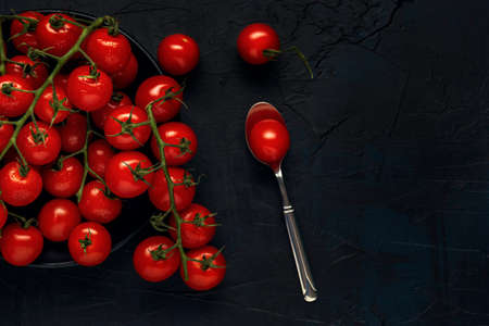 Multiple trusses of red wet cherry tomatoes in black plate and dessert spoon on a dark textured background. Top view. Flat lay. Space for text.