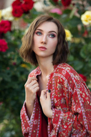 Young beautiful dreamy woman poses in the rose garden.