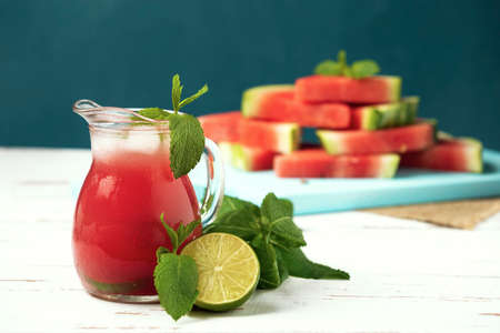 Glass jug with ice-cold watermelon juice, lime, mint and watermelon slices on the white wooden Provence style table.