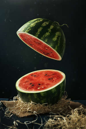 Sliced watermelon flying under dark rustic table. Floating objects. Levitation of vegetable pieces in the dark room. 写真素材