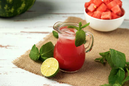 Glass jug with ice-cold watermelon juice, lime, mint on the burlap napkin.