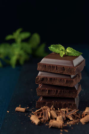 Heap of chocolate pieces with mint on the dark wooden table.