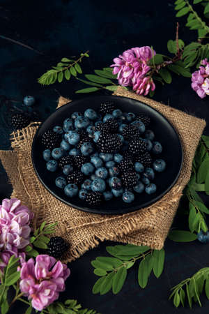 Black plate with blueberry, blackberry and acacia flowers on the burlap napkin and the dark background.