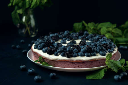 Cottage cheese pie decorated with blackberry, blueberry and mint leaves on the dark textured background.