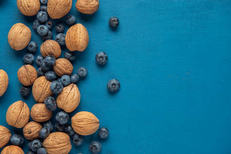 Close-up walnuts and blueberry on the blue background. Flat lay. Copy space.